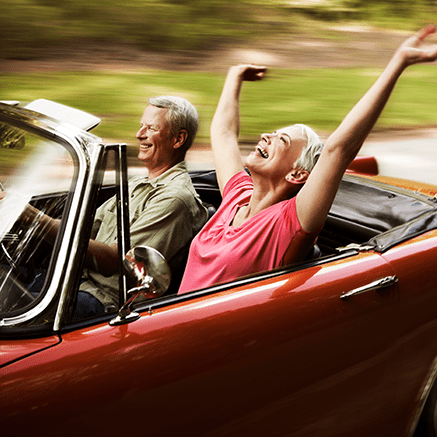couple driving in convertible car