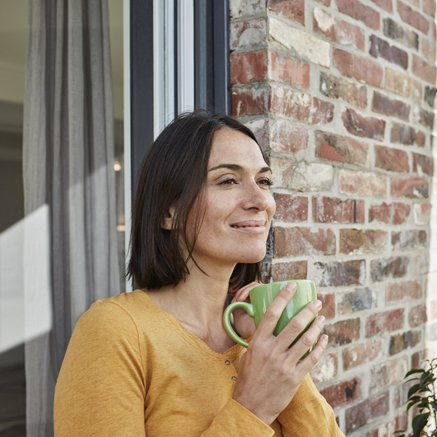 woman standing outside drinking coffee