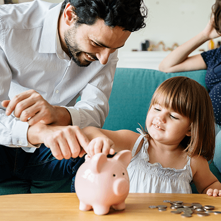 father and daughter putting coins in piggy bank