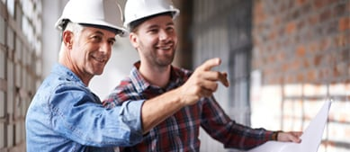 two men with hardhats looking at blueprints
