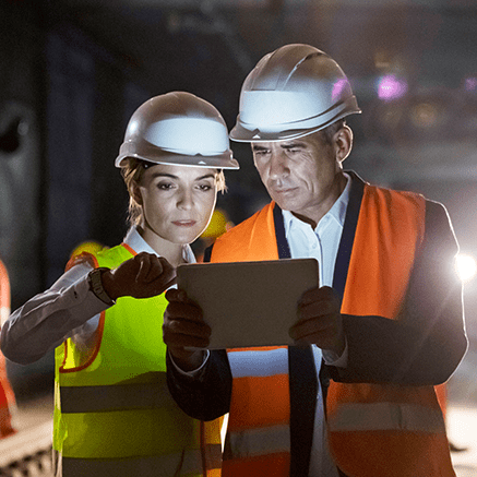 female and male with hardhats looking at tablet