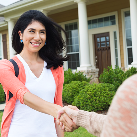woman shaking hands with real estate agent outside of new home