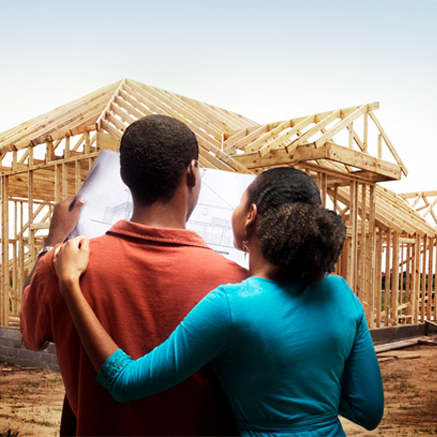 couple standing in front of home being constructed