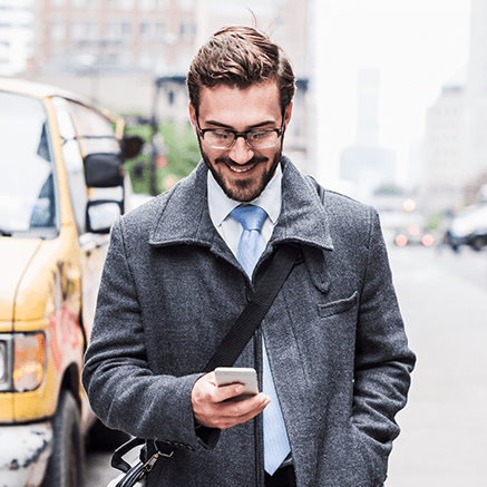 business man on busy street looking at phone