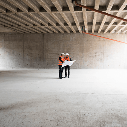 two people on construction site looking at blueprints