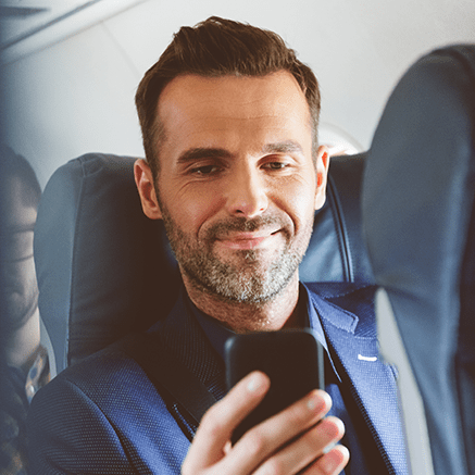 man on plane using cell phone